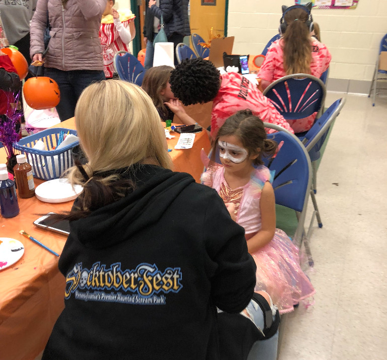 Female TCHS student paints a domino mask on a little girl for Beaver Creek's Trunk or Treat event.