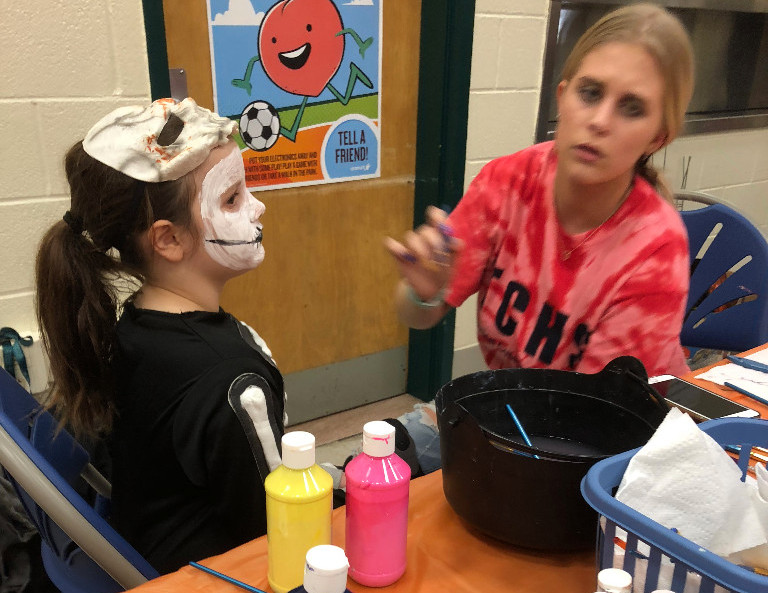 Female TCHS student paints a little girl's face for Beaver Creek's Trunk or Treat event.
