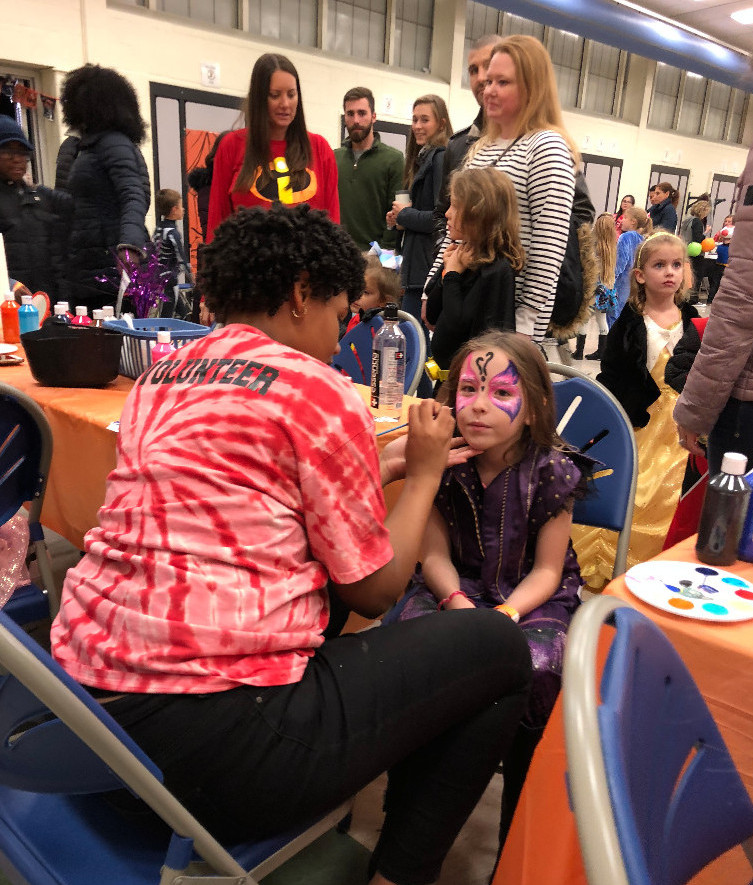 Female TCHS student offers face painting during Beaver Creek's Trunk or Treat event.